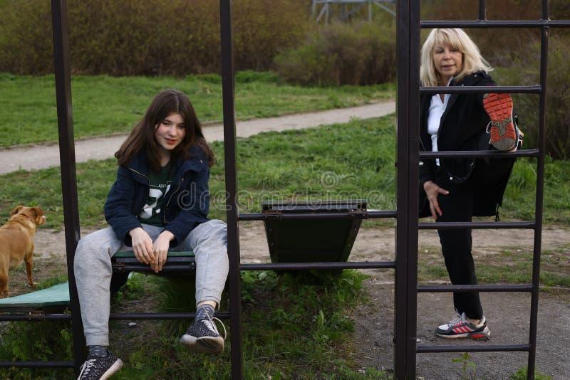 La fille et la femme de l'adolescence s'exercent sur l'endroit extérieur de gymnase en parc de ville photographie stock libre de droits