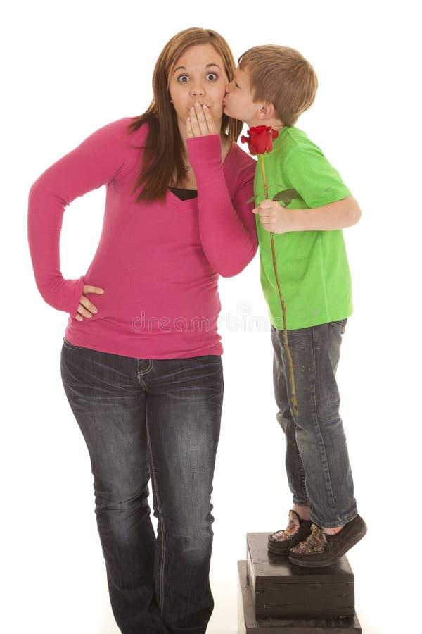 La fille et la jeune rose de prise de garçon embrassent la joue photo stock