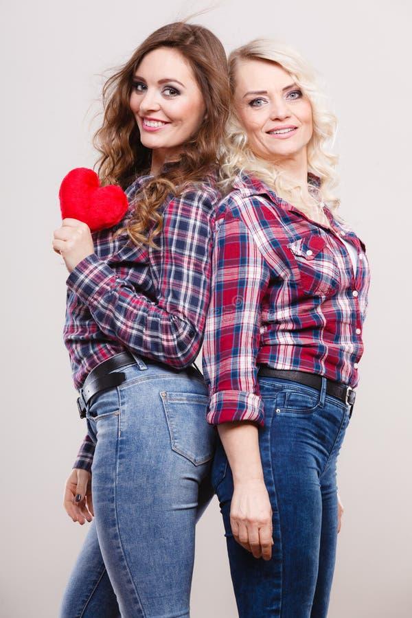La fille et la mère adultes avec le coeur aiment le signe photographie stock