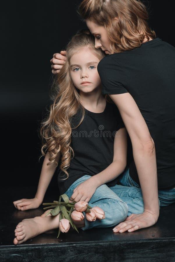 La fille et la mère avec la tulipe fleurit étreindre sur le noir photos libres de droits