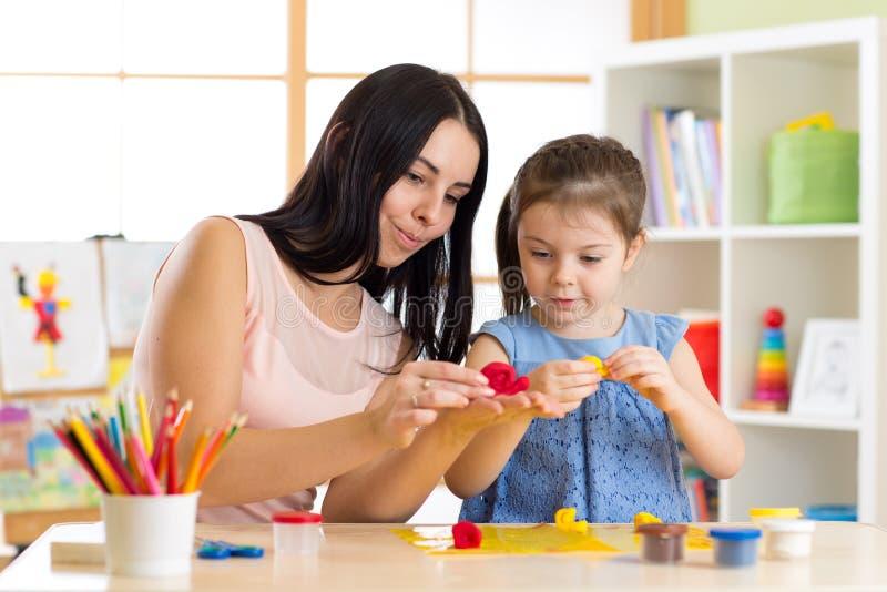 La fille et la mère d'enfant d'enfant jouent les jouets colorés d'argile dans la crèche à la maison photographie stock libre de droits
