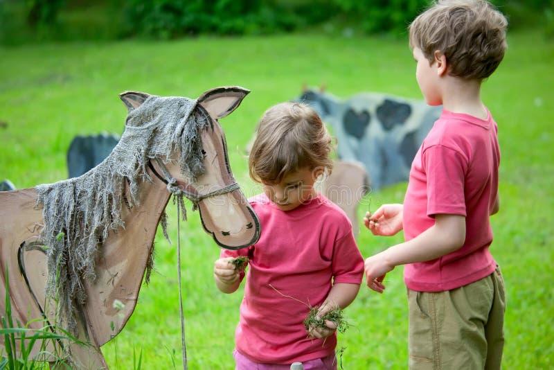 La fille et le garçon alimentent un cheval en bois image stock
