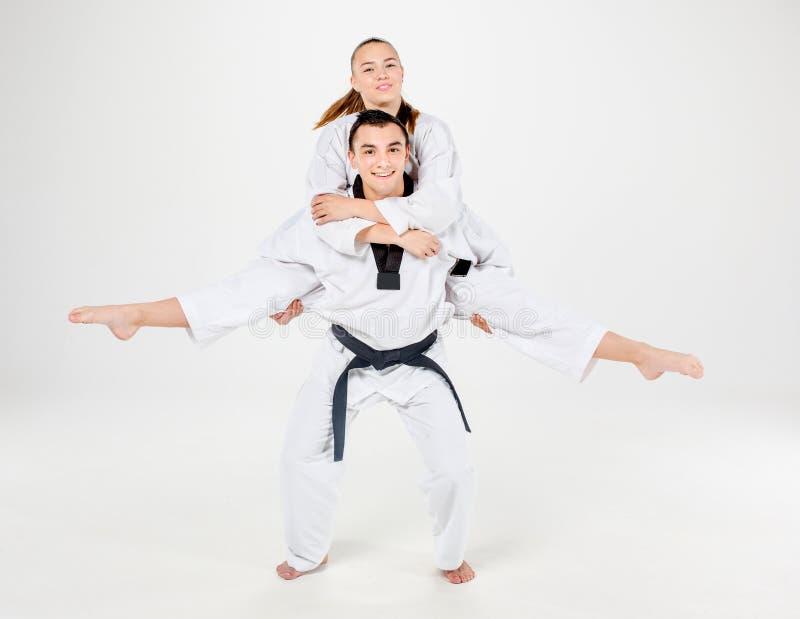 La fille et le garçon de karaté avec les ceintures noires photographie stock