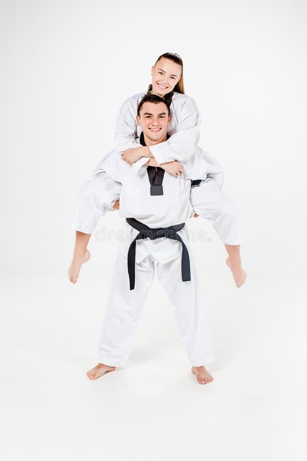 La fille et le garçon de karaté avec les ceintures noires image stock