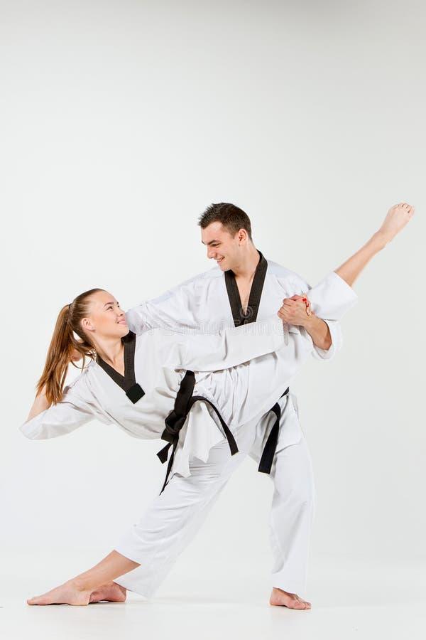 La fille et le garçon de karaté avec les ceintures noires photo stock