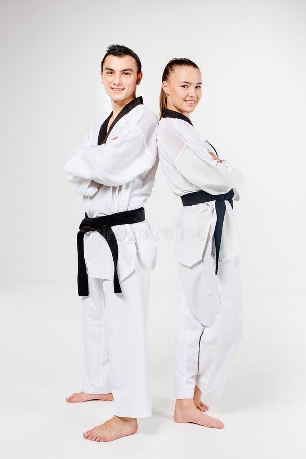 La fille et le garçon de karaté avec les ceintures noires photo libre de droits