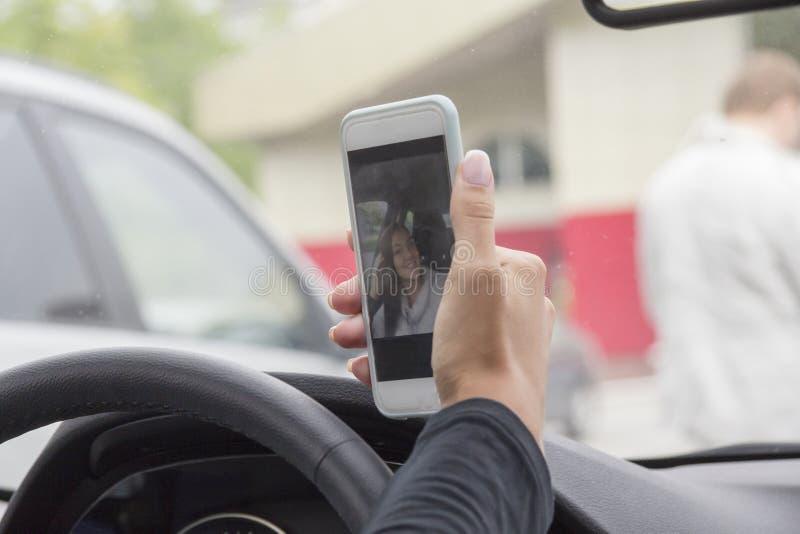 La fille et le téléphone dans la voiture photographie stock