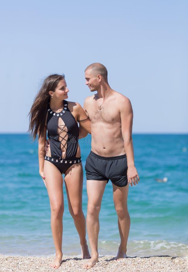 La fille et le type marchent le long de la mer regardant chacun autre photos stock
