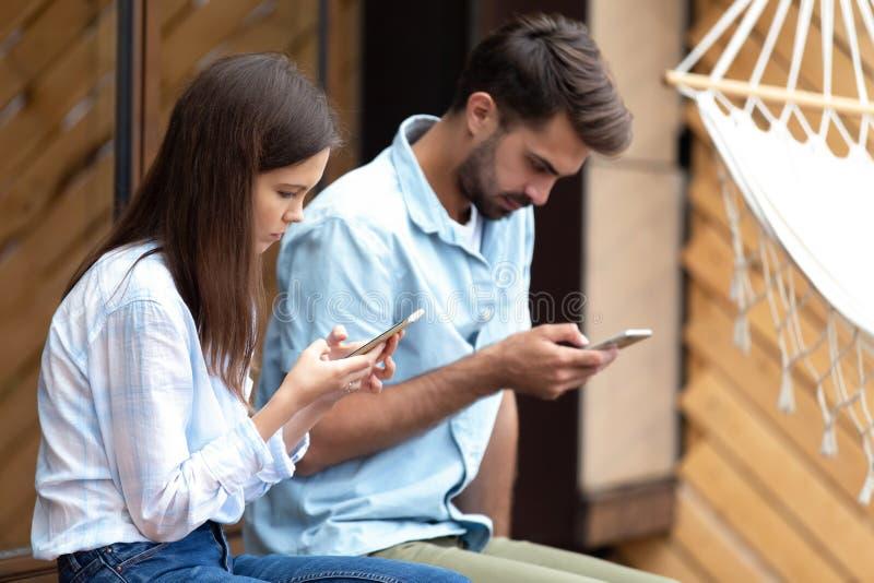 La fille et le type tenant des smartphones passent en revue l'Internet causant en ligne photographie stock