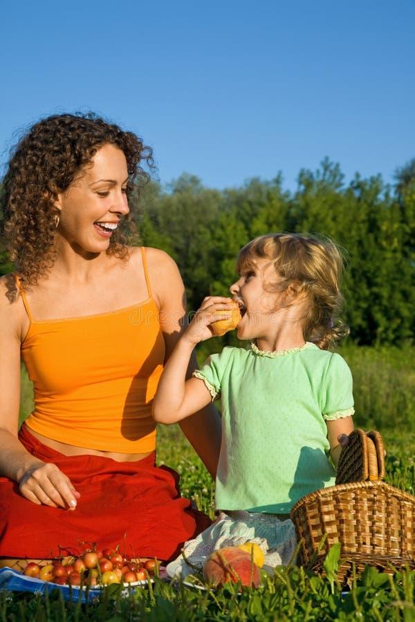La fille et les jeunes femmes mange des fruits sur le pique-nique photographie stock libre de droits