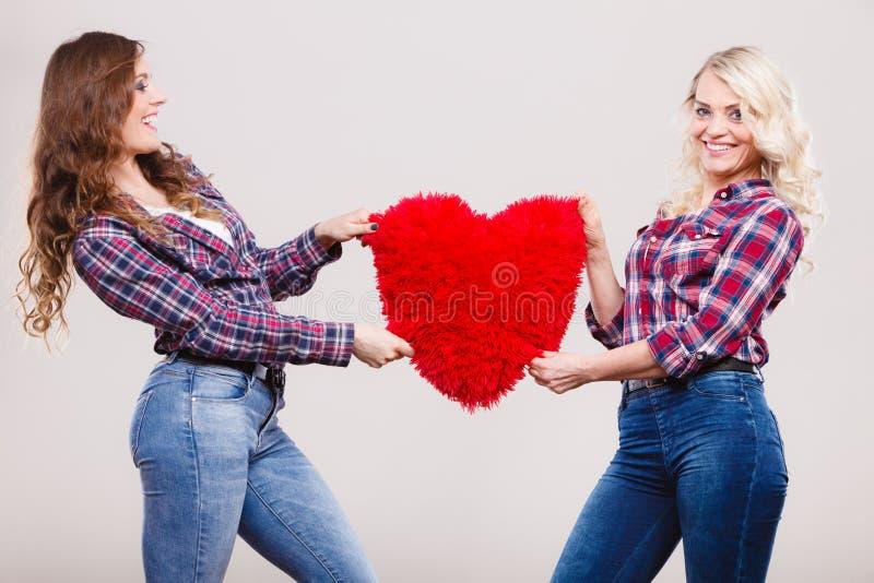 La fille et la mère adultes avec le coeur aiment le signe photos stock