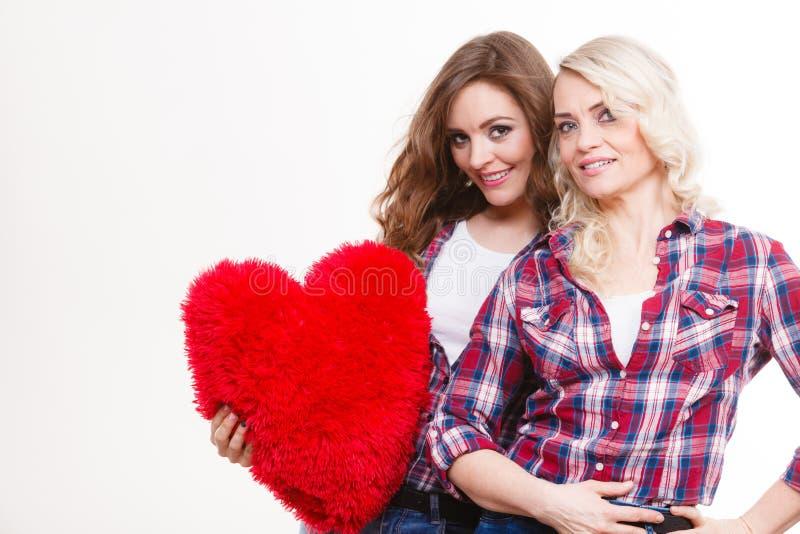La fille et la mère adultes avec le coeur aiment le signe images stock