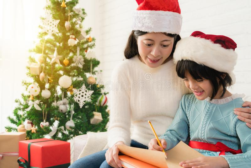 La fille et sa mère écrivent la lettre ensemble photographie stock