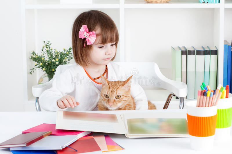 La fille et un chat ont lu un livre d'images photo stock