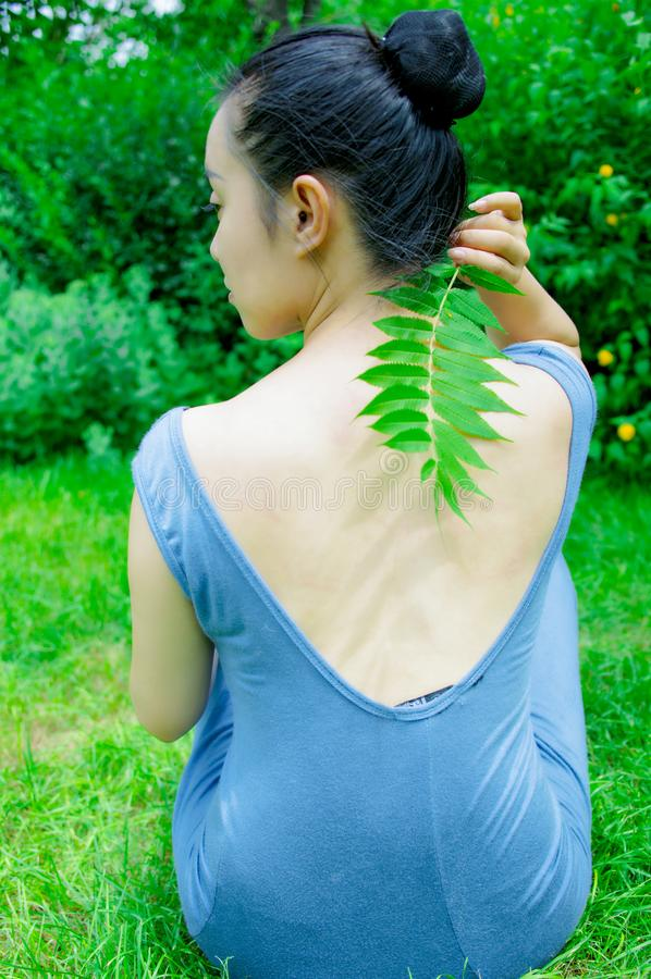 La fille a eu les feuilles vertes dans sa main photos libres de droits