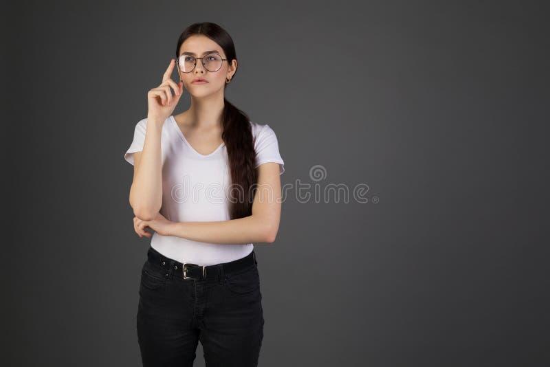 La fille européenne ne peut pas lire le signe, mettant sur des verres louchant et fronçant les sourcils en tant que regarder foca photos stock