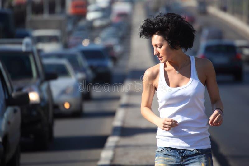 La fille exécute sur le milieu d'omnibus dans la ville, vue sur la courroie photos stock