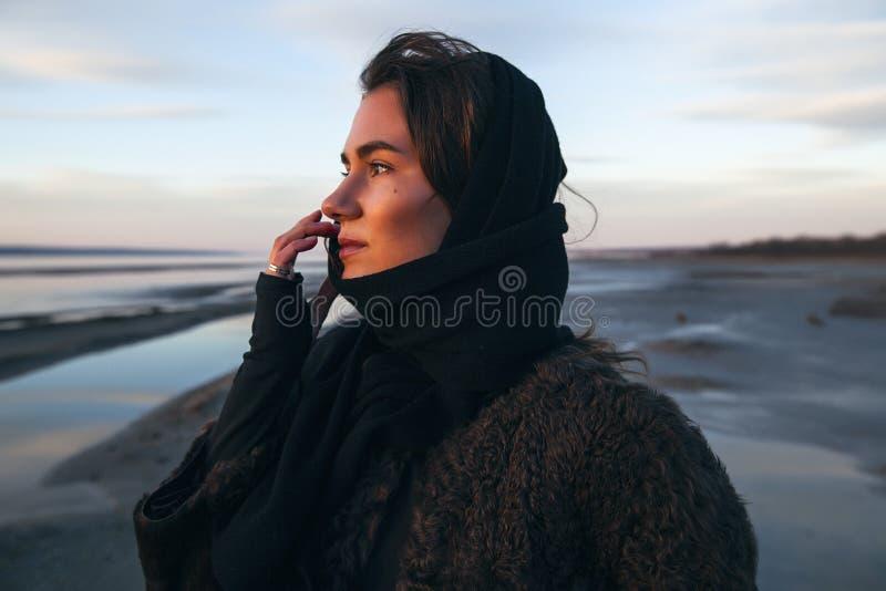 La fille extérieure de portrait dans un manteau marche sur le lac, fille dans une écharpe photos stock