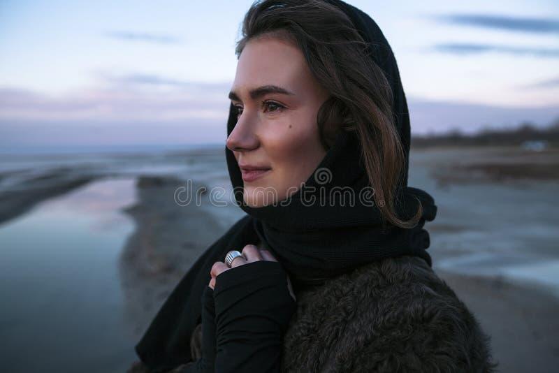 La fille extérieure de portrait dans un manteau marche sur le lac, fille dans une écharpe photos libres de droits