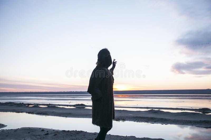 La fille extérieure de portrait dans un manteau marche sur le lac, fille dans une écharpe image libre de droits