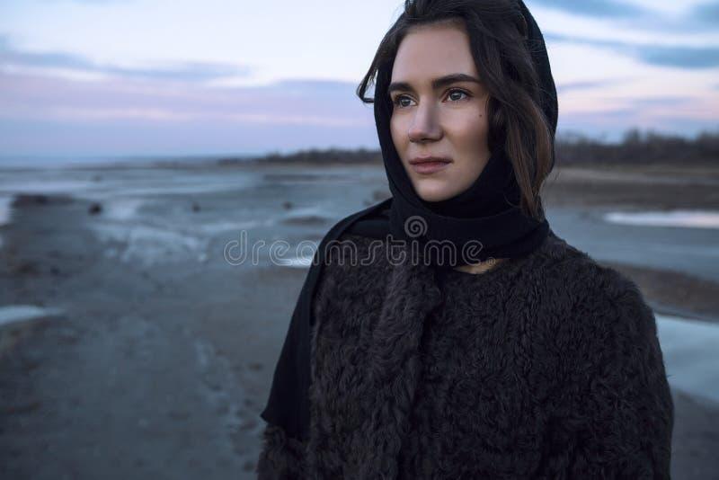 La fille extérieure de portrait dans un manteau marche sur le lac, fille dans une écharpe image stock