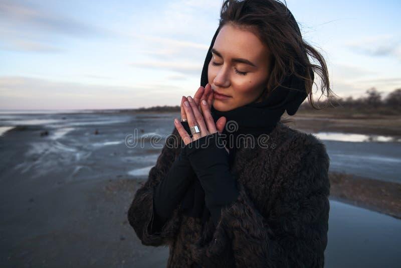 La fille extérieure de portrait dans un manteau marche sur le lac, fille dans une écharpe photographie stock libre de droits