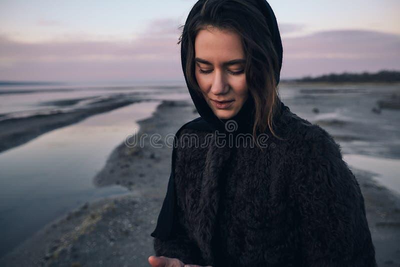 La fille extérieure de portrait dans un manteau marche sur le lac, fille dans une écharpe photo stock