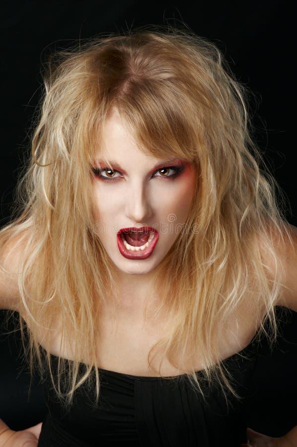 La fille fâchée dans le studio avec les languettes rouges photographie stock