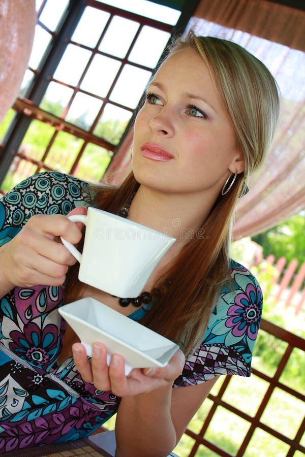 La fille fair-haired retient une cuvette blanche dans des mains images stock