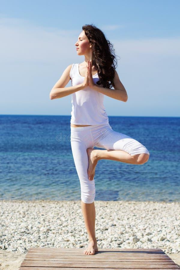 La fille faisant le yoga s'exerce sur la côte photos libres de droits