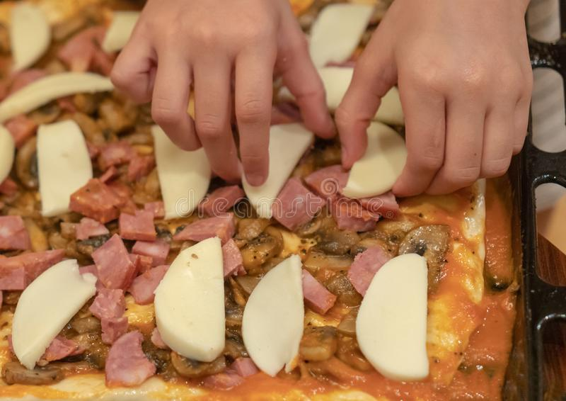 La fille fait cuire la pizza Les mains de l'enfant présentent des tranches de fromage de mozzarella sur une pizza photos stock