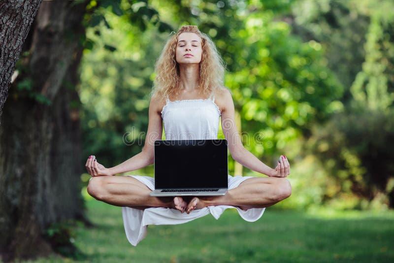 La fille fait de la lévitation avec l'ordinateur portable photographie stock