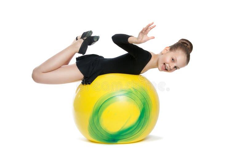 La fille fait des exercices sur un grand ballon jaune photo libre de droits