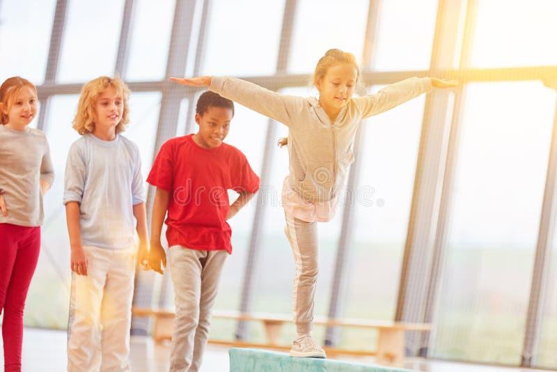 La fille fait la gymnastique dans la classe de gymnase image stock