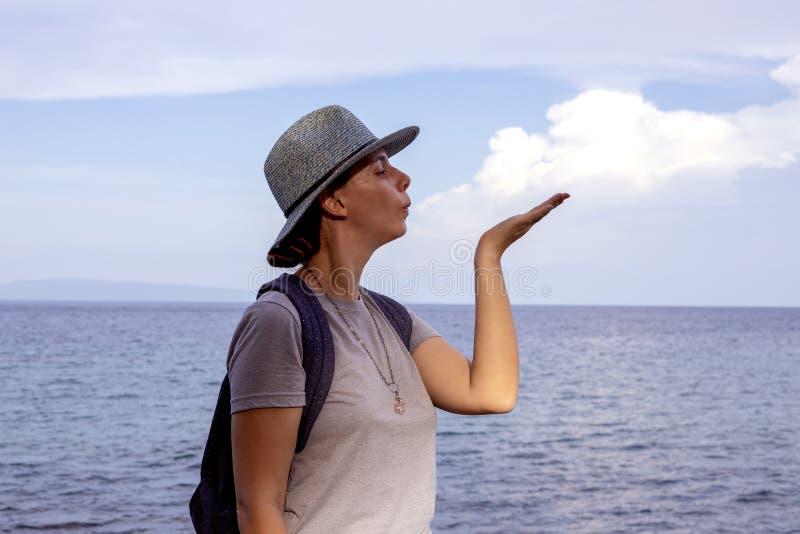 La fille fait sauter un nuage au-dessus de mer Pose modèle sur le fond tropical de mer Voyageur marin dans le chapeau du soleil image stock