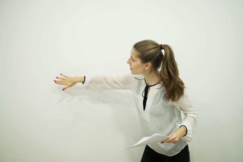 La fille fait une présentation et se tient d'un mur blanc image libre de droits