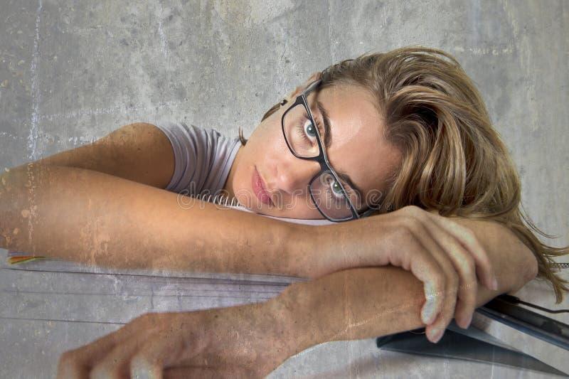 La fille fatiguée attirante et belle d'étudiant se penchant sur la pile de livres d'école a fatigué et était ennuyeuse après l'ét photo stock