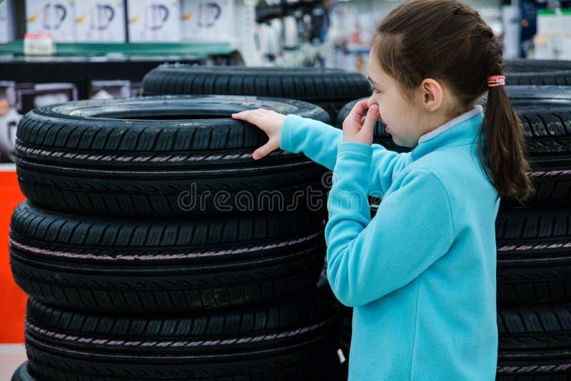 La fille ferme son nez de l'odeur désagréable du caoutchouc, pneus sur la fenêtre de boutique à vendre images stock