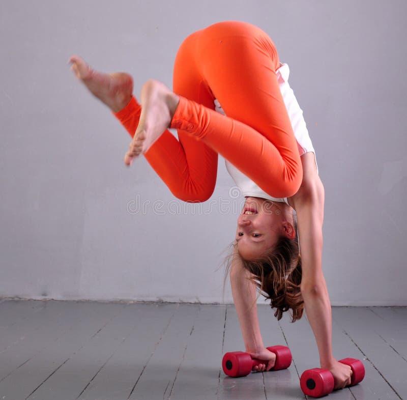 La fille folâtre adolescente fait des exercices pour se développer avec des muscles d'haltères sur le fond gris Concept sain de m image stock