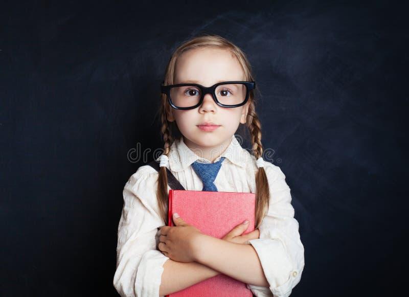 La fille futée d'enfant dans l'uniforme scolaire vêtx avec le livre rouge photos stock