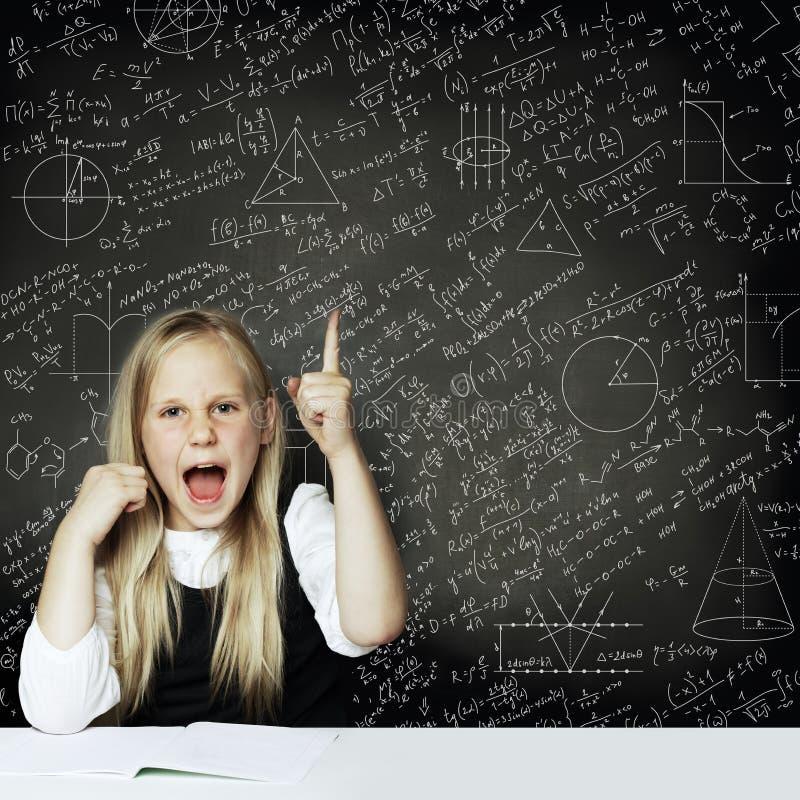 La fille futée mignonne d'étudiant d'enfant ont l'idée fond de tableau noir avec des formules de la science Étude du concept de l images libres de droits