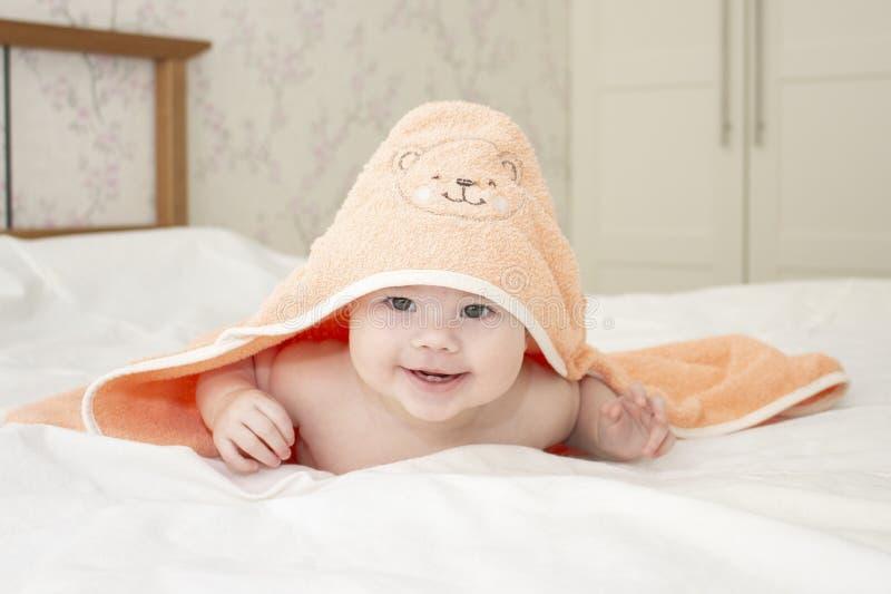 La fille gaie de bébé garçon regarde de dessous l'enfant caucasien de serviette 6 mois de portrait examinant le foyer mou de camé images libres de droits