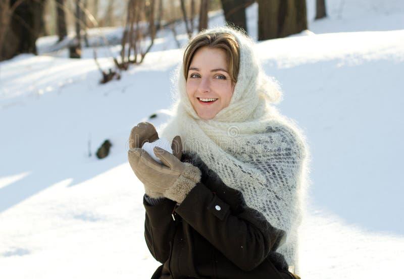 La fille gaie en hiver tricoté d'écharpe jette l'hiver de Russe de neige photographie stock libre de droits