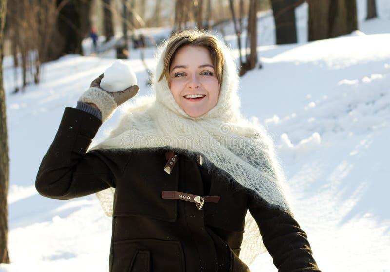 La fille gaie en hiver tricoté d'écharpe jette l'hiver de Russe de neige images libres de droits
