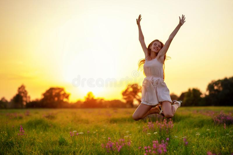 La fille gaie heureuse saute sur la nature au-dessus du coucher du soleil d'été photographie stock libre de droits