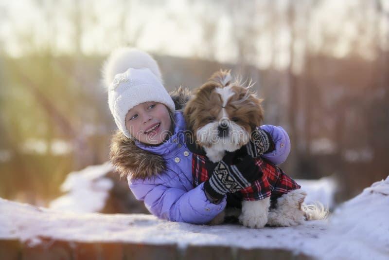 La fille gaie mignonne étreint son chiot le jour d'hiver de promenade photos libres de droits