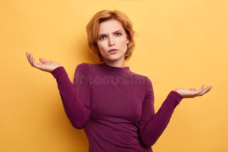 La fille gesticule des épaules pendant que le doesn t connaissent la réponse de la question photo libre de droits
