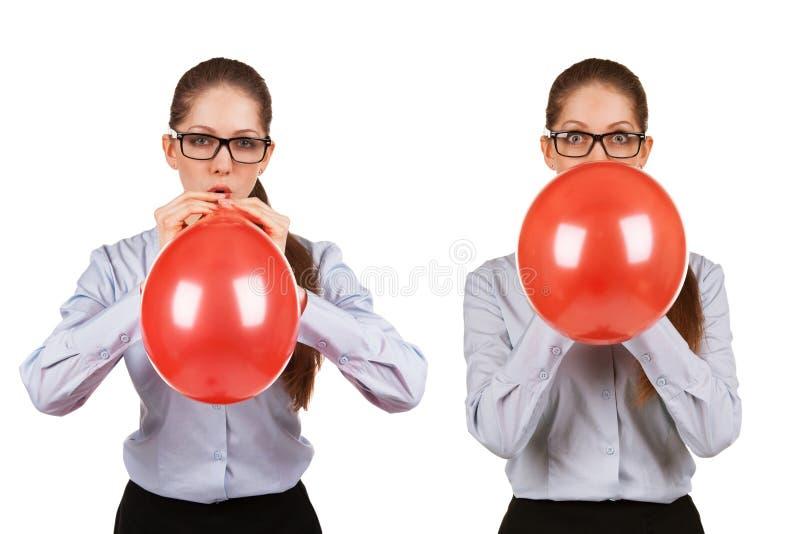 La fille gonfle une boule rouge image stock