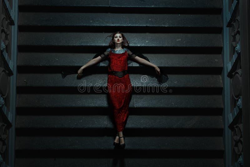 La fille gothique est tombée sur les escaliers la nuit photos stock