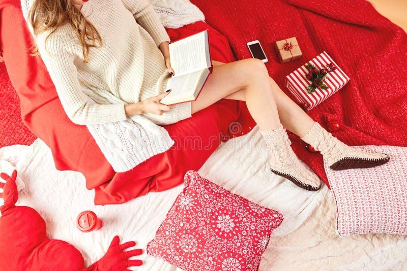 La fille a habillé la robe tricotée et les mensonges tricotés de chaussettes et lit un livre sur les couvertures et les oreillers photo stock